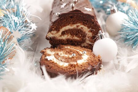 christmas yule log and decoration- festive chocolate pastry with cream