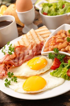 english full breakfast with fried egg, bacon,toast, coffee and fruits Stock Photo