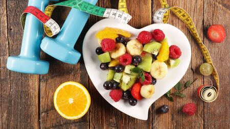 healthy food concept with fruit salad and dumbbell