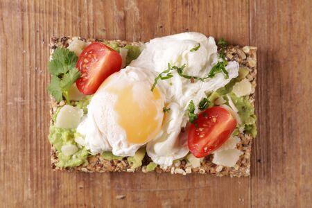 bread slice with avocado, poached egg, tomato and cheese on wooden board Reklamní fotografie