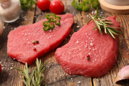 raw piece of beef with herb and pepper Фото со стока