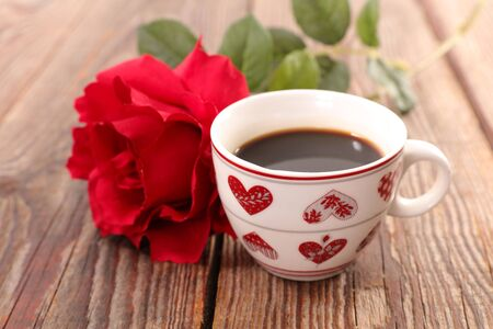 coffee cup and red rose on wood background Фото со стока