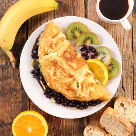 omelet with blueberries, fruit and coffee cup