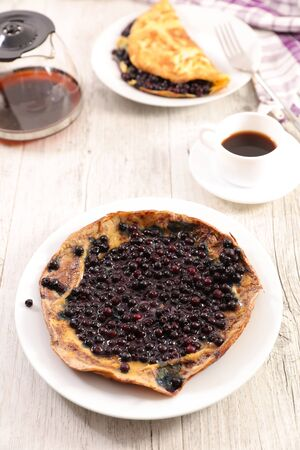 omelet with blueberries and coffee cup