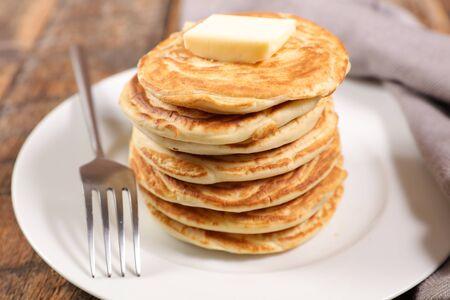 Montón de panqueques con mantequilla sobre fondo de madera