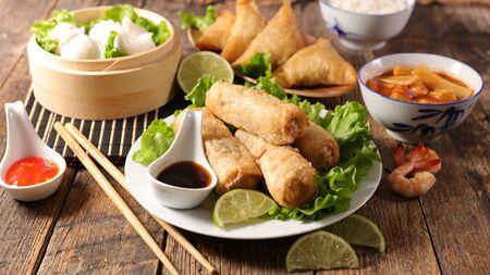 surtido de comida asiática: rollito de primavera, sopa de fideos, dim sum Foto de archivo