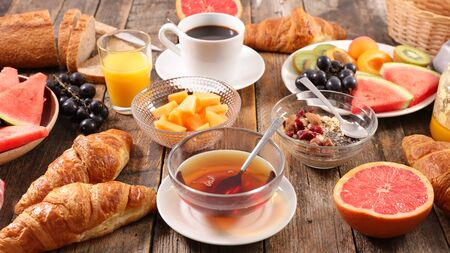 full breakfast with coffee cup, tea cup, croissant, bread and fruit