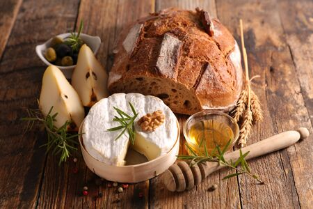 bread, camembert, honey and pear on wood background