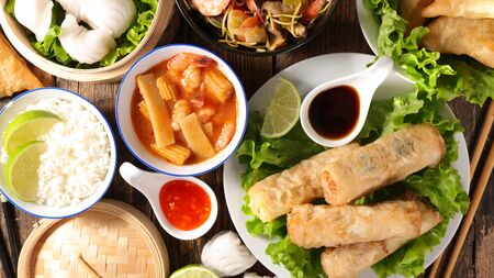 assorted of asian dishes- spring roll, chinese soup, rice and fried noodles