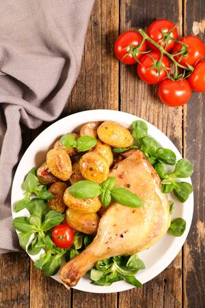 grilled chicken leg with potato and lettuce Фото со стока