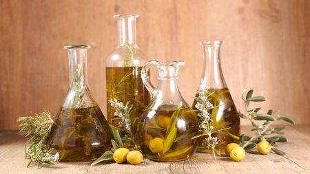 assorted of olive oil in bottle with branch, rosemary