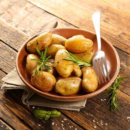 roasted potato and rosemary on wood background Фото со стока