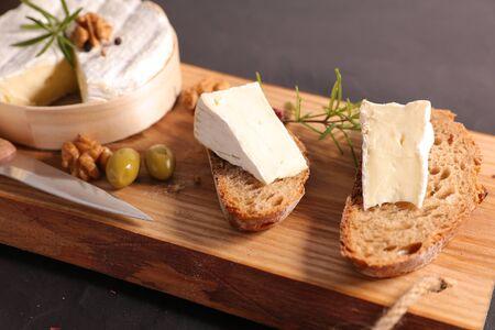 bread slice with camembert on wooden board Фото со стока