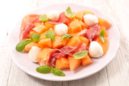 melon salad with mozzarella, prosciutto ham and basil
