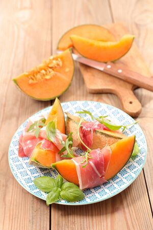 melon slices with prosciutto ham and basil Stok Fotoğraf