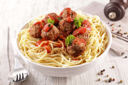 bowl of spaghetti with meatball, tomato sauce and cheese