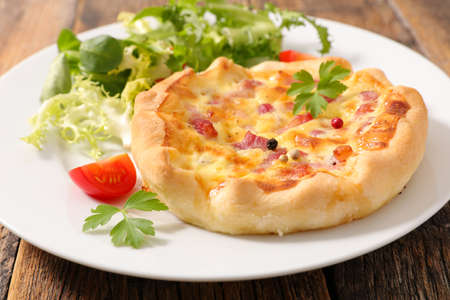 quiche lorraine and lettuce on plate
