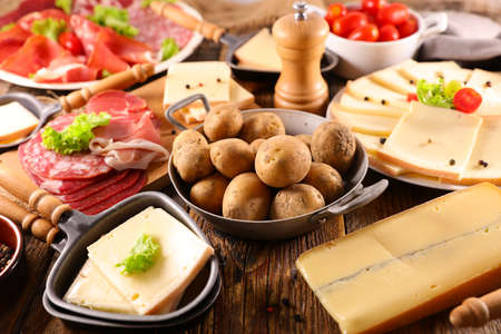 traditional raclette cheese party on wood background Stock fotó