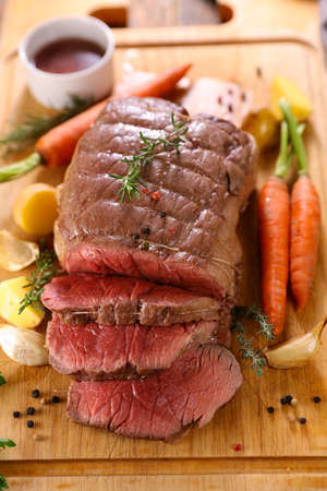 roast beef with vegetable on wooden board