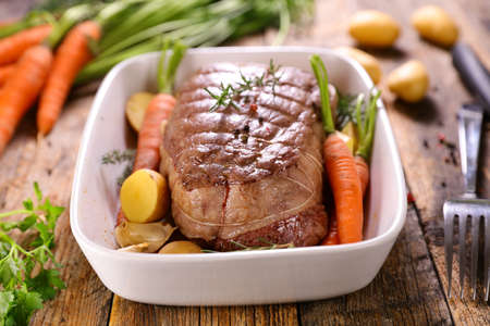 roast beef with vegetable on wood background