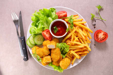 plate with chicken nugget, french fries and vegetable salad 版權商用圖片