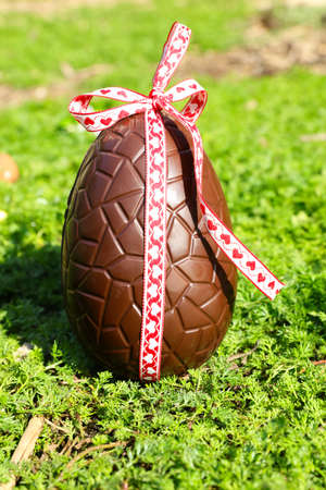chocolate easter egg with ribbon in the garden