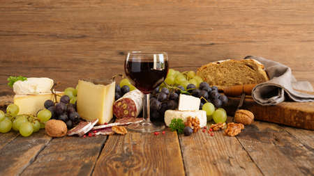 glass of wine, cheese, grapes and salami