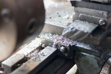 metalworking industry: working on a lathe with flying sparks. Lathe