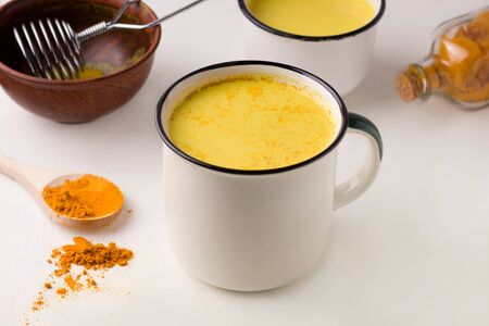 two mugs of golden milk next to turmeric on a white table