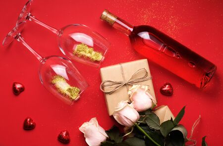 holiday concert with wine, gifts from craft paper, sweets and flowers on a red background. Suitable for Women's Day or Valentine's Day