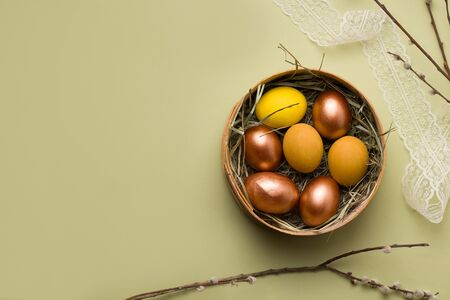 Easter eggs of copper and yellow in a nest on a pale green background. There is copy space.