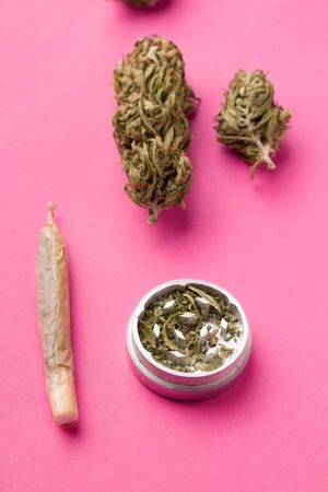 a jamb with marijuana and whole hemp next to a grinder on a pink background Imagens