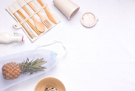 cutlery made of bamboo next to an eco bag on a linen background with copy space. zero waste concept and freedom from plastic