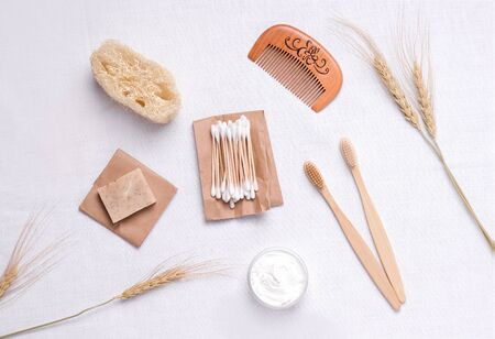 ecological bath accessories such as toothbrushes, hairbrush, soap, washcloth made of bamboo, glass and wood on linen fabric. zero waste concept 免版税图像