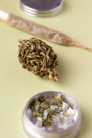 marijuana on a green background next to a cigarette and grinder. Imagens