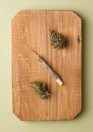 marijuana on a wooden board next to a cigarette