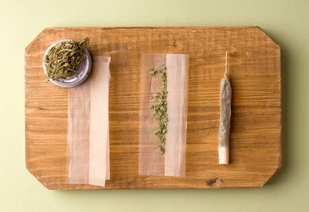 cooking cigarettes with marijuana on a wooden board