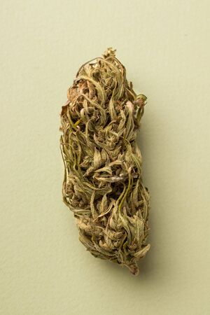 dried marijuana on a green background close-up. vertical photo Imagens