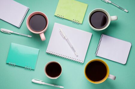 working pattern of pens, notebooks and cups of coffee on a mint background