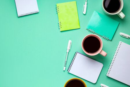 mint green background copy space with work accessories such as notebook, pens, coffee Stok Fotoğraf