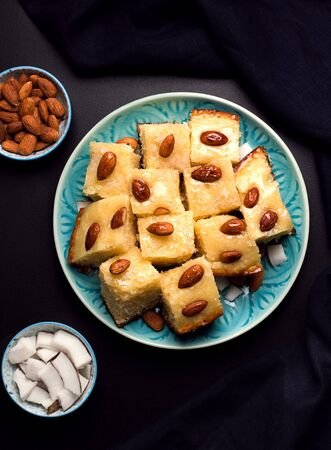 oriental cuisine confectionery semolina pie with syrup, coconut and almonds arabic Busbus on a black background Imagens