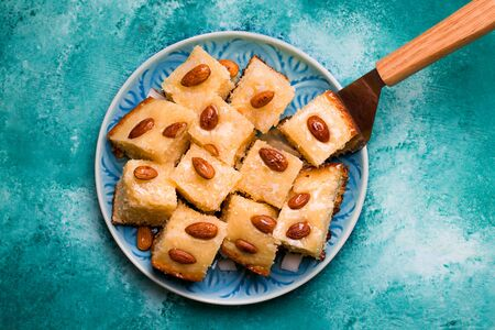 oriental cuisine confectionery semolina pie with syrup, coconut and almond arabic Busbus on a blue plate with a shovel. Imagens