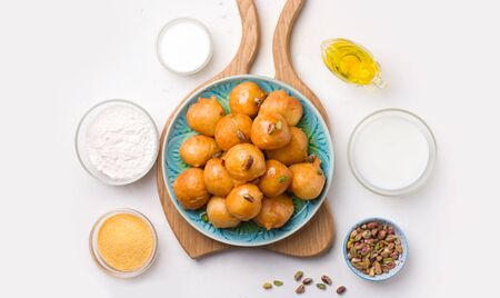 Lokma recipe a traditional arabic dessert. Sweet fried balls on a plate on a white plate next to the ingredients.