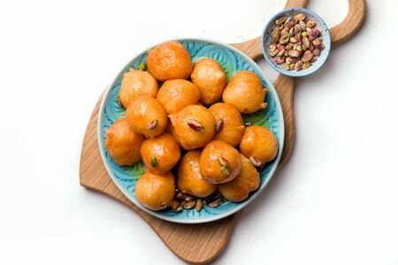 Lokma is a sweet dish in Greek, Turkish, Persian and Arabic cuisines. Dessert of sweet fried balls in a plate close-up on a white background