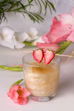 A drink with a shiny shimmer decorated with strawberry wedges next to flowers