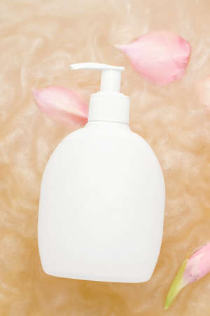 Mockup of cosmetic products. White dispenser bottle in shiny water