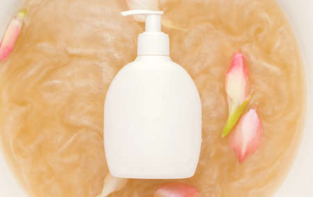 Mockup of cosmetic products. White bottle in water with shimmer and flower buds