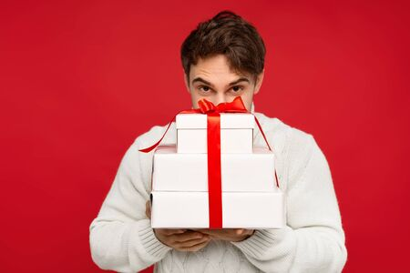 man in white sweater with obscure face holding Christmas presents isolated on red background. Christmas concept 免版税图像