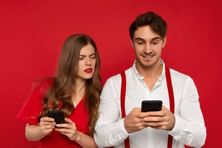 worried elegant woman looking at boyfriend smartphone, stand closely to each other against red background. Youth with modern technologies. Addicted couple Banque d'images