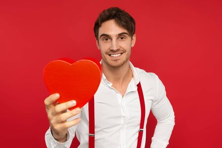 smiling handsome man in suspender and shirt holding heart shaped box isolated on red background, valentines concept Banque d'images